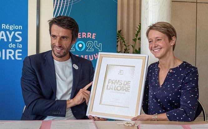 """Tony Estanguet et Laurence Garnier tiennent un cadre avec le label """"Terre de jeux 2024"""""""